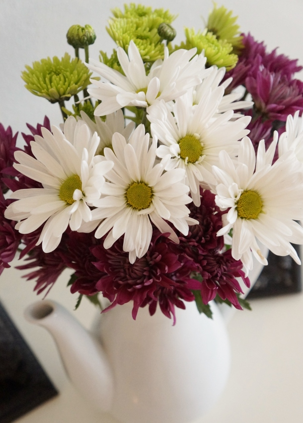 Teapot filled with fresh daisies